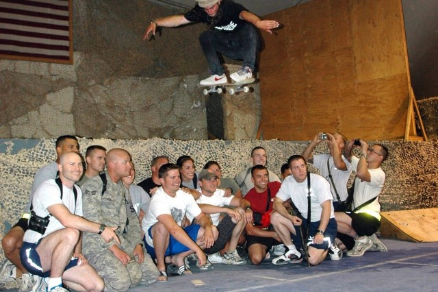 Extreme skater and snowboarder, Danny Kass, jumps over a group of service members on his skateboard at the Morale, Welfare and Recreation clamshell on Bagram Air Field, Afghanistan, June 28. Kass, Grete Eliassen and Nate Holland visited BAF on a morale tour but wound up getting their own extreme Soldier experience through a visit of the air field's hospital, a Humvee egress assistance trainer and live-weapons drills with Special Forces servicemembers on the air field's firing range.