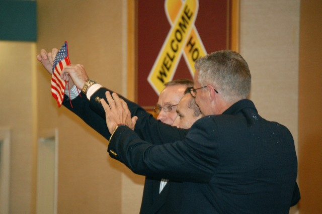 Fort Sam Houston, Texas (July 7, 2008) - From left to right, Thomas Howes, Marc Gonsalves and Keith Stansell hold up an American flag during their Yellow Ribbon Ceremony Monday at Brooke Army Medical Center. They were held captive in Colombia by the Revolutionary Forces of Colombia (FARC) for more than five years.