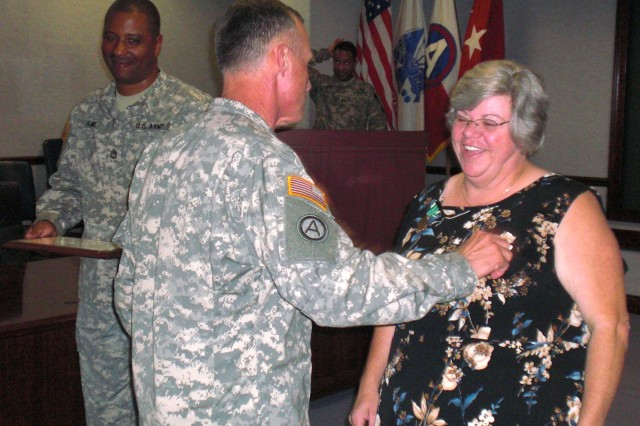 Lt. Gen. James Lovelace, U.S. Army Central Commanding General, awards Audrey Moss, USARCENT senior stock fund budget analyst, the Commander's Award for Civilian Service, June 18, at Fort McPherson. Among her record of excellence during her nine years with USARCENT, Moss saved the Army nearly a half-billion dollars in cost avoidance through identification of errors in the Funds Control Module