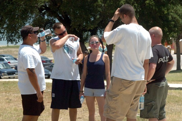 Soldiers from 1st Battalion, 7th Cavalry Regiment, 1st Brigade Combat Team, 1st Cavalry Division, and their families cooled off with water before taking to the field for a softball game. The event was part of the unit's early Independence Day celebrations held July 2 at the Belton Lake Outdoor Recreational Area.