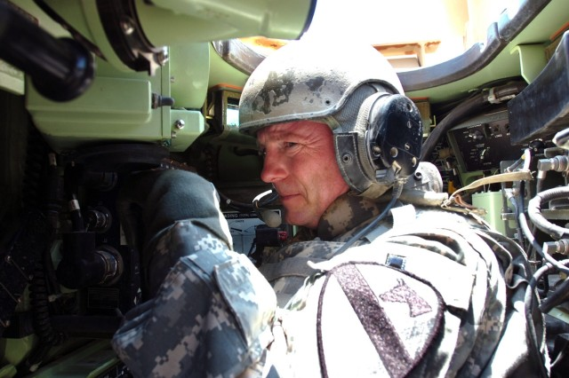 """Colonel Douglas Gabram, commander of the 1st Air Cavalry """"Warrior"""" Brigade, 1st Cavalry Division, who normally flies through the air in an AH-64D Apache attack helicopter, adjusts to the cockpit of the an M2A3 Bradley during an air/ground integration training event at Fort Hood, Texas. Gabram, a native of Cleveland, was able to glean what the Bradley Soldiers go through as well as what they see on the ground."""