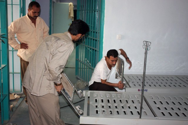 Iraqi workers assemble equipment in the Nasiriyah Prison's medical ward. The prison is near Tallil Air Base and COB Adder. The new, maximum-security prison is nearing completion and is already able to receive prisoners from Nasiriyah.