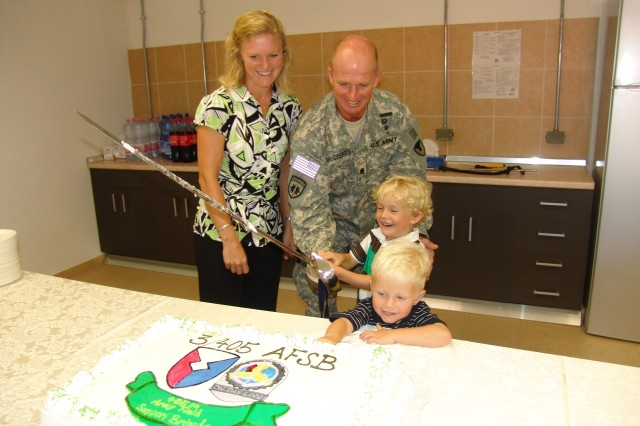 Tammy and Lt. Col. Roger McCreery cut the cake at the reception following the 3/405th AFSB change of command ceremony. They were assisted by their sons Kaden and Rylan.