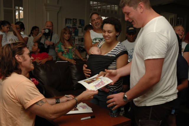 SCHOFIELD BARRACKS, Hawaii - Billy Ray Cyrus hands an autographed photo to Spc. Chris Palo, WTB and wife Cynie during the meet and greet at the Warrior Assistance Center during the July 4th festivities. Cyrus met with many wounded warriors and their family members, signing autographs and engaging each in conversation.