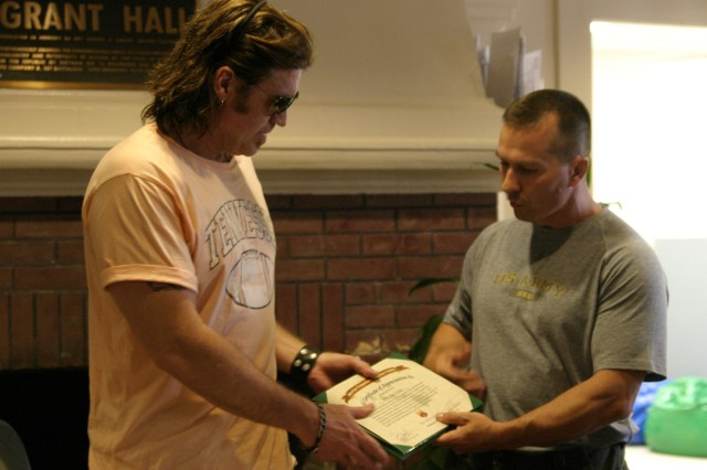 SCHOFIELD BARRACKS, Hawaii - Warrior Transition Battalion Commander Lt. Col. Harold Xenitelis honors Billy Ray Cyrus with a certificate of appreciation for his visit to the wounded warriors and their family members.