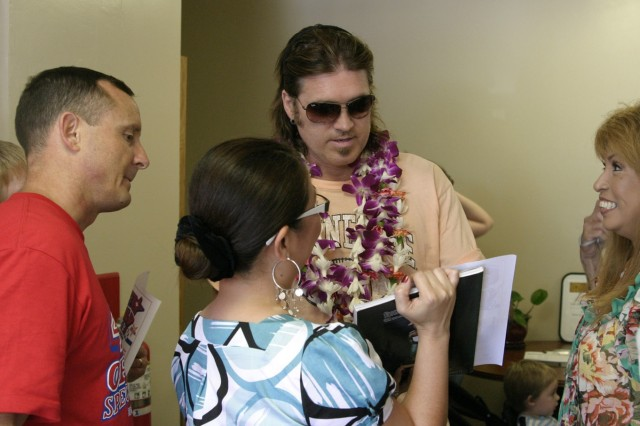SCHOFIELD BARRACKS, Hawaii - A group of people crowd around Billy Ray Cyrus outside the Warrior Assistance Center. Cyrus signed autographs and posed for pictures as he made his way into the center for a meet and greet with the wounded warriors.