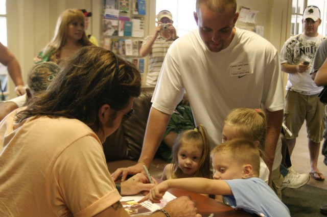 SCHOFIELD BARRACKS, Hawaii - Sgt. Richard Montgomery, Warrior Transition Battalion, watches as his son Brennen shows Billy Ray Cyrus where to autograph his photograph. Montgomery, along with his daughters Kaia and Felicity (l-r) and wife Lyndse (not pictured) joined other members of the WTB for a chance to meet the famous country singer.