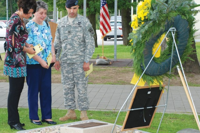 Capt. Renato Vieira, 554th Military Police Company commander, shows Kathy Brelsfoard, left, and Carol Ann Clifton, both of Decatur, Ill., a memorial plaque honoring Cpl. Karen Clifton, Brelsfoard's niece and Clifton's granddaughter. Clifton, 22, was killed in Baghdad, Iraq, June 21, 2007, when a rocket-propelled grenade hit her vehicle and exploded. Building 2914 on Panzer Kaserne, the home of the 554th MPs, was renamed Clifton Hall at a ceremony June 20.