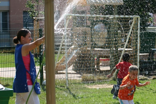 Arlene Rodriguez, a lead teacher with the U.S. Army Garrison Schweinfurt Child development Center, helps children cool off on the playground. The CDC recently obtained its accreditation from the National Association for the Education of Young Children.