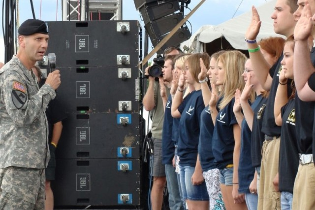 Brig. Gen. Jeffrey E. Phillips, deputy chief of Army Public Affairs, administers the oath of enlistment to 100 future servicemembers on the main stage at Country USA, a three-day music festival in Oshkosh, Wis., June 28, 2008.