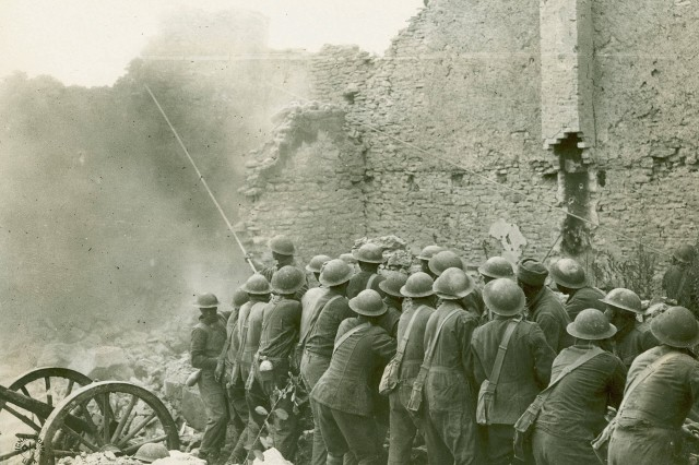American engineers pull down battered walls of a building and use the rubbish to mend the roads that traverse the old trenches in the captured salient. Sept. 14, 1918.