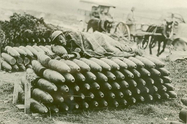Cpl. Sampson G. Morse of Company G, 808th Pioneers, taking a nap on a pile of shells. Between Esnes and Montzeville, Meuse, France. Oct. 12, 1918.