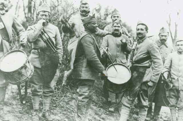 Cpl. Frank Sandis of 315th Pioneer Infantry putting a little American 'pep' into a Frenchman's drum. Glorieux, Meuse, France. Jan. 4, 1919.