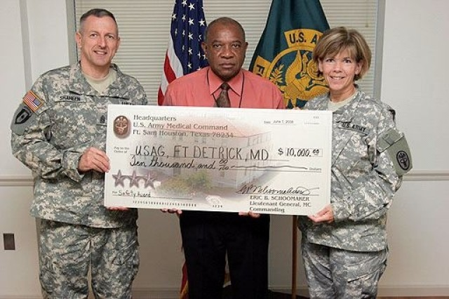 Command Sgt. Maj. James Shaheen, Rudy Spencer, safety director and Col. Mary Deutsch, garrison commander, display the $10,000 check presented to the Fort Detrick safety office June 12 at the Association of the United States Army medical conference in San Antonio, Texas.