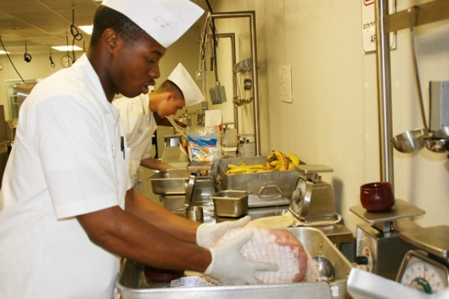 Pvt. Brandon Osazuwa prepares a roasted turkey while Pvt. Christopher King figures out how much rice he needs to make during students' second day of therapeutic diet preparation at the Department of Medical Sciences' Nutrition Education and Training Branch.