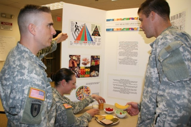 Staff Sgt. Kevin Lindsey, instructor/writer, explains the food pyramid, which includes suggested servings of vegetables meats and drinks, to Pvts. Destiny Finch and Ian Middleton at the Department of Medical Sciences' Nutrition Educatin and Training Branch.