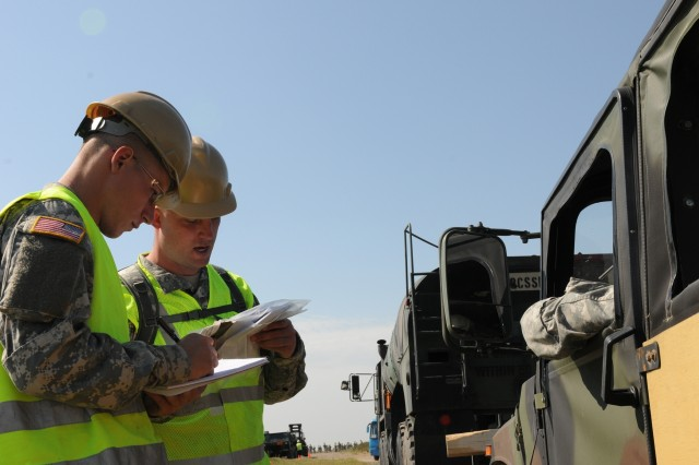 Spc. Michael Stokes and Pvt. Daniel Edwards verify the paperwork of an incoming vehicle during railhead operations in Romania.