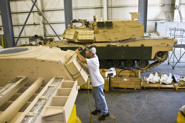 Brett Waite, an Anniston Army Depot mechanic, installs defensive armor onto the turret of an Assault Breacher Vehicle. The turret is fabricated by the depot and assembled atop an overhauled M1 Abrams chassis to create an ABV for the United States Marine Corps. The manufacturing of ABVs shows the depot's capability to build and overhaul vehicles for the joint military. The first ABV completed under full-rate production here was delivered to the USMC on July 7.