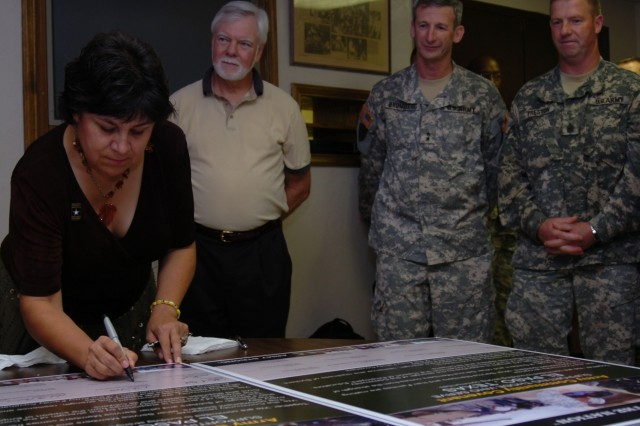 Susana Chaparro, the wife of Kenneth D. Miyagishima who is the Mayor of Las Cruces, N.M., signs the Army Community Covenant between the communities surrounding Fort Bliss.