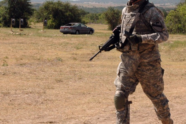 Sgt. 1st Class James Maxwell, with Company A, 3rd Battalion, 8th Cavalry Regiment, 3rd Brigade Combat Team, 1stt Cavalry Division from Manistique, Wis. completes the final leg of an exhausting timed training exercise that included various firing positions, dragging a 200 pound mannequin, and carrying a 100 pound rucksack. The unit stayed at the range on Fort Hood for two days, returning July 1.