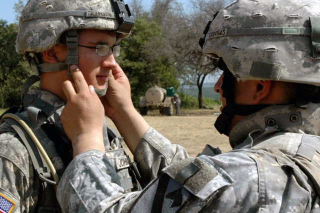 Pfc. Kyle Johnson, a tank crewmember with Company C, 3rd Battalion, 8th Cavalry Regiment, 3rd Brigade Combat Team, 1st Cavalry Division from Waterloo, Iowa has his chin strap adjusted by Staff Sgt. Kevin Barrantes, from Queens, N.Y., a tank commander also with Company C. The unit spent two days at the range on Fort Hood last week, finishing with a timed stress shoot designed to exhaust the Soldier's bodies and minds, forcing them to think several steps ahead.