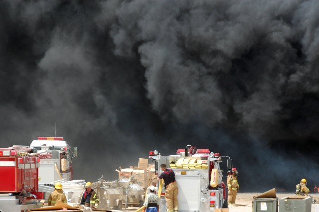 Fighting against 100-degree temperatures and 20 MPH winds, members of the Area Support Group-Kuwait Fire Department battle a blaze in the defense Reutilization and Marketing Office yard at Camp Arifjan, Kuwait, July 12, 2008.  No one was injured, and the early-morning fire was under control by 11 a.m.  The cause of the fire is under investigation. ""