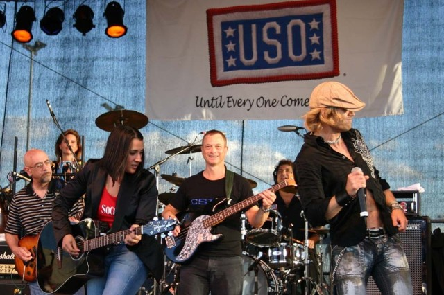 Gina Gonzalez, Gary Sinise, and Jeff Vezain perform as part of the Lt. Dan Band at U.S. Army Garrison Schweinfurt, Germany, July 7. Sinise is also co-founder of Operation Iraqi Children, which provides school supplies to children in areas being served by deployed U.S. forces, such as Iraq and Afghanistan. Last fall, the 1st Squadron, 91st Cavalry (Airborne), headquartered in Schweinfurt, distributed 2,048 school supply packages to children in Afghanistan.