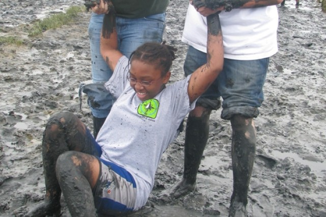 Aja Brown, from Wiesbaden Germany, is assisted by fellow campers after getting up close and personal with an endless supply of mud found on the German island of  Langeoog, where 78 children of deployed servicemembers spent a week as part of Camp A.R.M.Y Challenge.