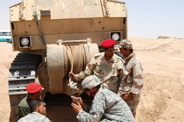 Sgt. 1st Class David Sullivan, an engineer equipment supervisor from the 326th Engineer Battalion, Fort Campbell, Ky., trains Iraqi army engineers on the use of the U.S. Army's D7 armored bulldozer at Contingency Operating Base Speicher, Iraq, June 26. The 326th is on duty in Iraq under the command and control of U.S. Army Europe's 18th Engineer Brigade.