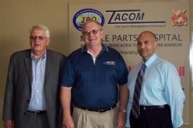 TACOM Life Cycle Management Command Industrial Base Operations Mobile Parts Hospital Program Manager Jim Uribe (right) Donald Casteel, contracting program manager, Honeywell, Inc., (left) and, Donald J. Hagarty, Ultra-Tech president, recognize completion of a TACOM LCMC Mobile Parts Hospital reset effort during a ceremony June 25 at Ultra Tech Machinery Inc., Cuyahoga Falls, Ohio.