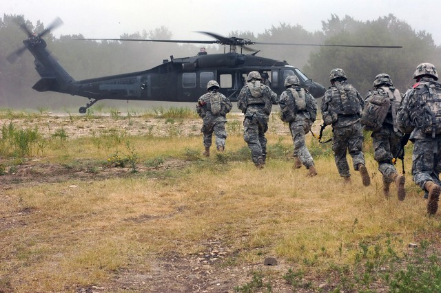 """Cavalry scouts from Troop B, 4th Squadron, 9th Cavalry Regiment, 2nd Brigade Combat Team, 1st Cavalry Division, prepare to board a UH-60 Black Hawk helicopter from 3rd Battalion, 227th Aviation Regiment, 1st Air Cavalry Brigade, 1st Cav. Div., after completing their mission as part of an air assault training operation dubbed """"Operation Dark Horse Lightning"""" at the St. Elijah Company Military Operations in Urban Terrain Site on Fort Hood, Texas June 30. """""""