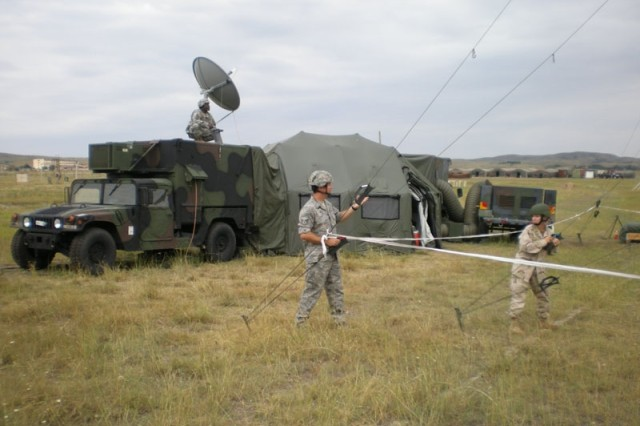 Tech Sgt. Chris Eder and MC1 Joyce Martin tighten the guide wires on an antenna for AFN-EuropeAca,!a,,cs Tactical Mobile Radio and Television System deployed to the Republic of Georgia for Immediate Response 2008.