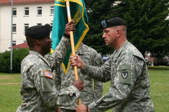 Lt. Col. Ronnie Bell, Jr. (left), the outgoing commander of the 1/405th Army Field Support Brigade, receives the battalion colors from Sgt. First Class Jon Cox during the battalion's recent change of command ceremony.