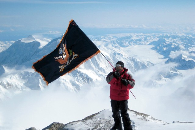 First Lt. Graham Ward, 1st Battalion, 24th Infantry Regiment, waves the battalion's colors at 17,200 feet during a Mount McKinley expedition.