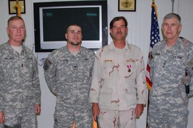 Command Sgt. Maj. Jeffrey Mellinger, AMC command sergeant major (far left) and Robert Blanton, Jr. (center left) join Robert Blanton, Sr. after he is awarded the Meritorious Civilian Service Award by Gen. Benjamin Griffin, AMC commander, May 21.