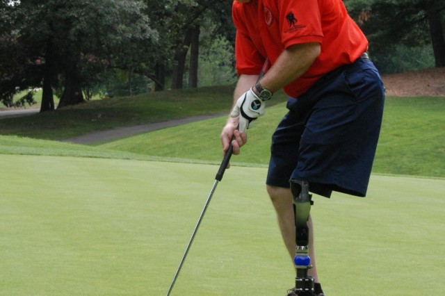 Retired Lt. Col. Dennis Walburn sinks a putt during the Congressional Charity Golf Classic Monday at Army-Navy Country Club in Arlington, Va. Walburn had his left leg amputated after an IED blast in Iraq. The golf tournament was a benefit for the Wounded Warrior Disabled Sports Project.