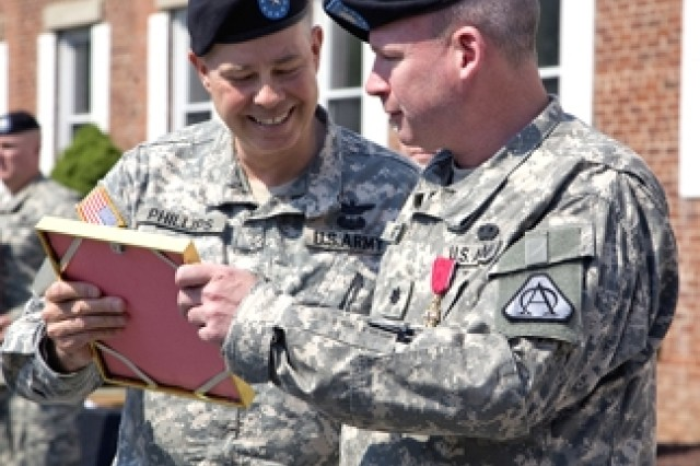 Brig. Gen. William N. Phillips (left) and Lt. Col. Brian Raftery review a congratulatory letter during Raftery's retirement ceremony.