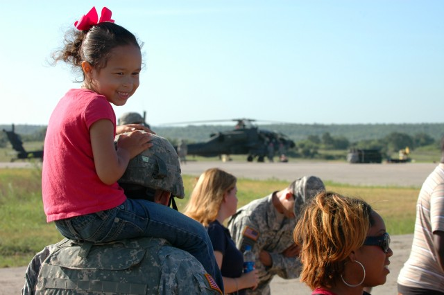 """Lily Cranford, 5, sits on her dad's shoulders during family day at a forward arming and refueling point at Fort Hood, Texas, July 12. Her dad, Biloxi, Miss., native Sgt. Derek Cranford, an armament specialist for Company D, 1st """"Attack"""" Battalion, 227th Aviation Regiment, 1st Air Cavalry Brigade, 1st Cavalry Division, took a break from loading rockets to give his daughter a couple extra feet of height so she could get a better view of the FARP."""