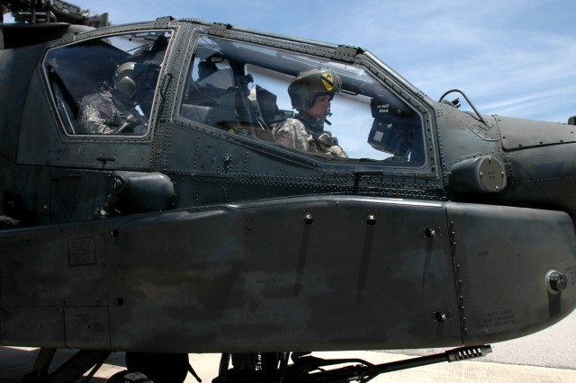 "Brigadier Gen. Frederick Rudesheim, the deputy commanding general (Support) for the 1st Cavalry Division, waits in the front seat of an AH-64D Apache attack helicopter piloted by Chief Warrant Officer 4 Frank Almeraz, the standardization instructor pilot for 1st ""Attack"" Battalion, 227th Aviation Regiment, 1st Air Cavalry Brigade, 1st Cav. Div, while the rotar blades come to a stop. Rudesheim visited the Attack troopers out in the field at a forward arming and refueling point during gunnery, July 12 at Fort Hood, Texas. Rudesheim would later fly out to a range and fire some of the weapons systems on the Apache."