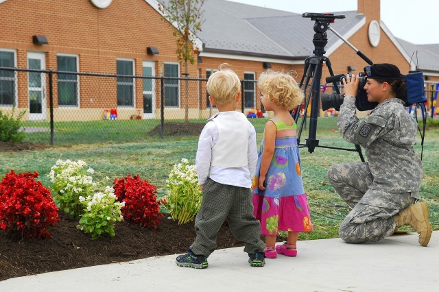 While the ribbon is cut at the Fort Myer Child Development Center, twin brother and sister Hunter and Sienna Bingham, 3, wait patiently for their playground to become available again while a Soldiers Media Center Soldier gets footage of the historic event.