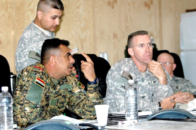 Maj. Gen. Jassem Nazal Qassim, commanding general of the 9th Iraqi Army Division, discusses security in the Mada'in Qada region with Col. Pat White, commander of the 2nd Brigade Combat Team, 1st Armored Division, during a meeting at Forward Operating Base Hammer, Iraq, July 8.