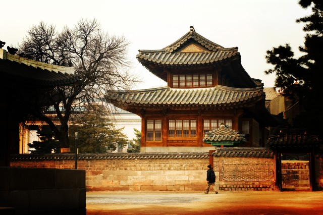 Visitors wander through the Deoksu Palace grounds amid towering reminders of Korea's royal past.