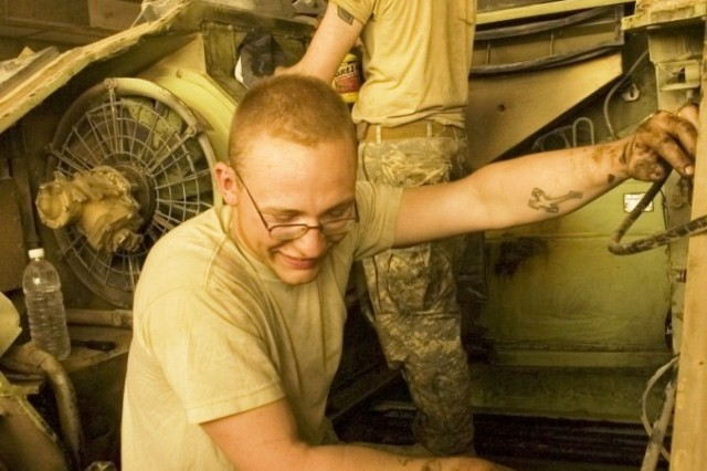 Pvt. Terrence Behanna, an infantryman with 2nd Battalion, 6th Infantry Regiment, works with another Soldier to clean out the engine compartment of a Bradley fighting vehicle at Combat Outpost Summers, Iraq, July 8, 2008. Sgt. David Turner, 4th Brigade Combat Team, 3rd Infantry Division.