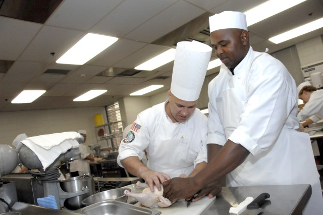 Staff Sgt. David Baisden (Left), instructor, shows student, Staff Sgt. Therus Nixon, how to prepare chicken for cutting.  Nixon is one of 13 students currently enrolled in the Advanced Culinary Training Course taught at the Army Center of Excellence, Subsistence, Fort Lee, Va.