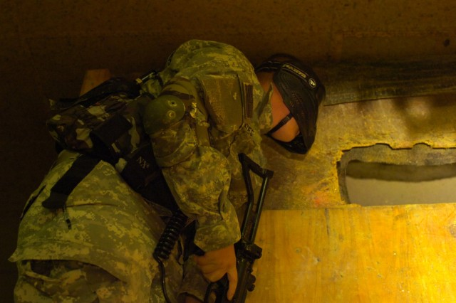 A Soldier and member of the 'Lethal Threat' paintball team peers out from a snipers nest over looking the battlefield. In scenario paintball, a hidden player with a quick trigger finger can remove the opposition one-by-one.