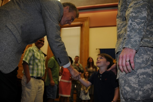 Kansas Lt. Gov. Mark Parkinson shakes the hand of 3-year-old Nicholas Dettmer, son of Capt. Travis Dettmer, 1st Infantry Division Public Affairs, July 16 at the state capitol in Topeka. The Dettmers were among three military Families who presented the lieutenant governor with a giant-sized card thanking Kansas state officials for being the first state to pass the Interstate Compact on Education Opportunities for Military Children.