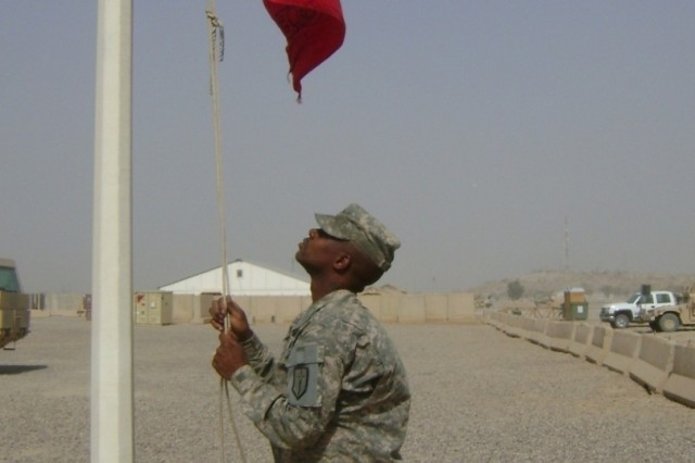"""CAMP LIBERTY, Iraq - Following the Transfer of Authority ceremony, Spc. Cedric Sutton, of HSC, 46th Engineer Combat Battalion raises the """"Steel Spike"""" flag over the 46th ECB (H) headquarters July 3 on Camp Liberty, Iraq. The 46th Eng. Bn. is assigned to the 926th Engineer Brigade serving with Multi-National Division Baghdad. The flag will be lowered when a new battalion takes over engineer operations in 2009. (U.S. Army photo by Capt. Patrick Jenkins, HSC, 46th ECB (H), 926th Eng. Bde., MND-B)"""