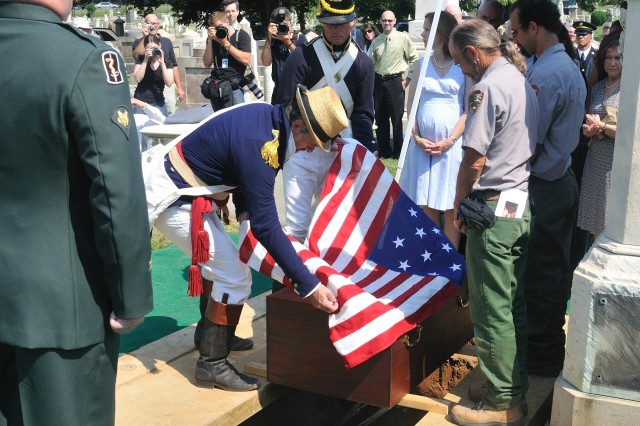 A small mahogany casket containing the remains of Maj. Gen. Alexander Macomb, a hero of the Battle of Plattsburg in 1814 and his wife Catherine is lowered into the newly reconstructed tomb at Congressional Cemetery July 17 by National Park Service employees and two park rangers dressed in historical uniforms.
