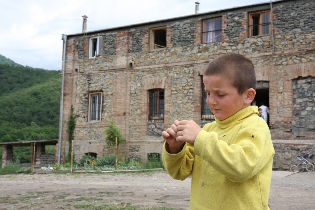 A special-needs child stands in front of the current, dilapidated childcare center in the Georgian town of Gremi. As part of EUCOM's humanitarian assistance program, the U.S. Army Corps of Engineers is building a new childcare center across the