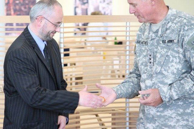 Peter Barth, the DistrictAca,!a,,cs regional program manager at Grafenwoehr, receives a coin from Lt. Gen. Robert Van Antwerp April 23 for his construction support.